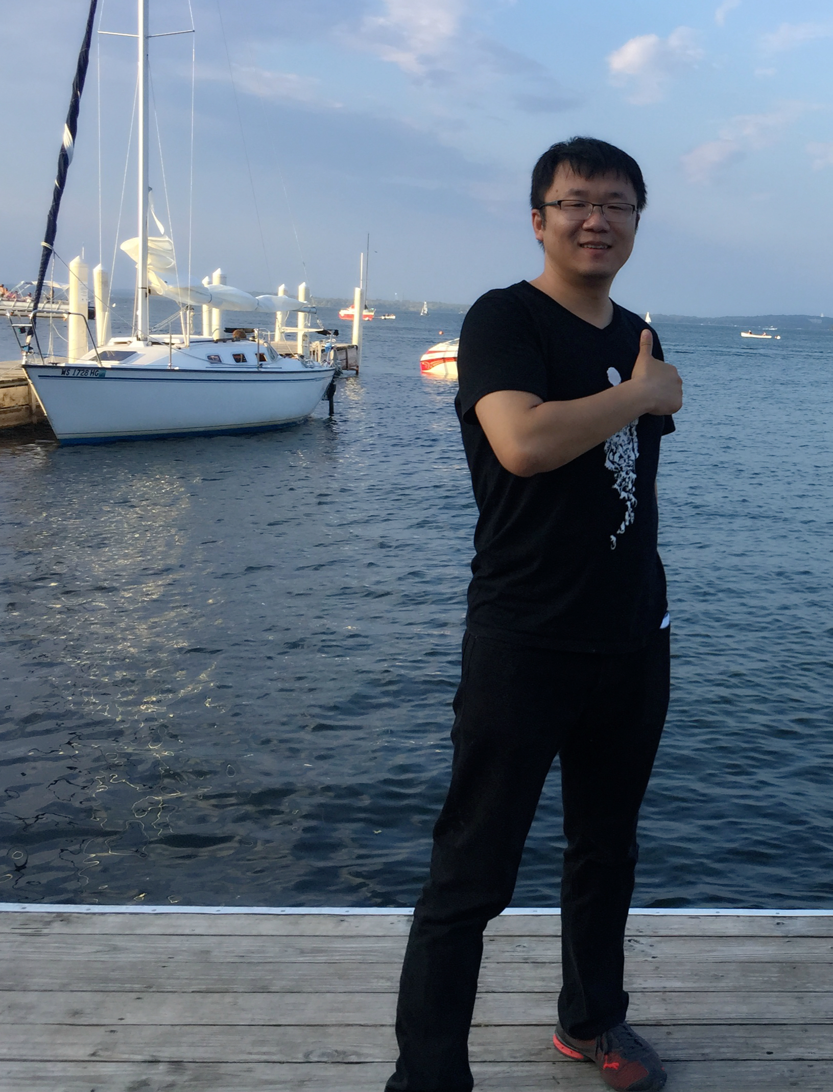 Dr. Peng Zhang standing in front of a boat